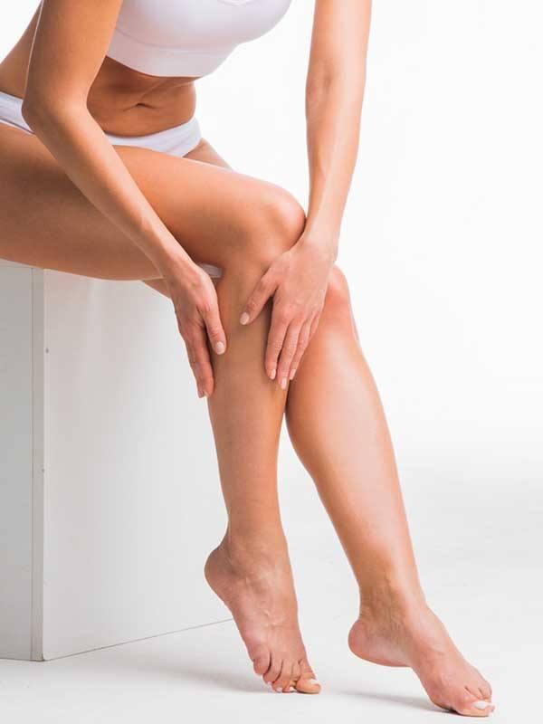 Bacaklarını tutan kalın bacaklı bir kadın
