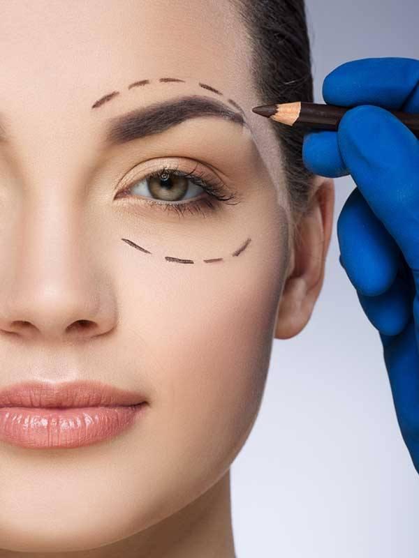 Migren tedavisi öncesinde sol göz çevresi işaretlenen genç kadın